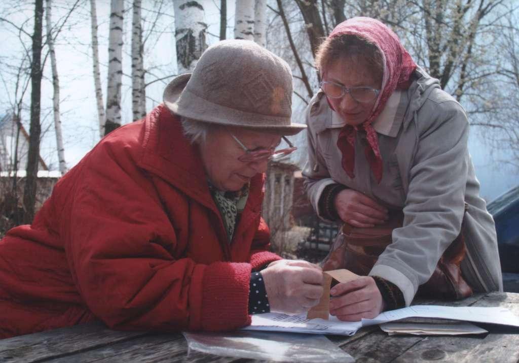 Роза Александровна Клепцова (слева) и Александра Васильевна Спицина рассматривают ленту медальона